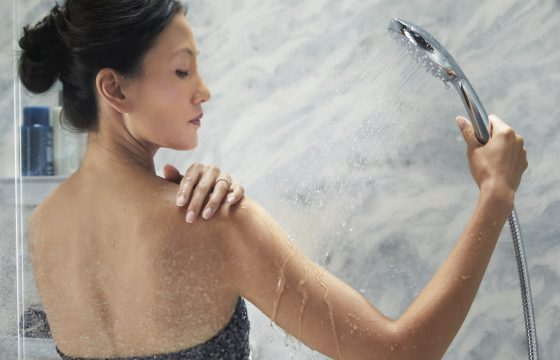 close up of woman using her luxstone handheld faucet to wash shoulders - new bluette walls