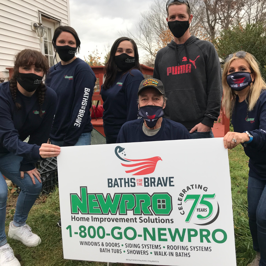 Baths for the Brave recipient holds NEWPRO sign with employees after completion of renovation