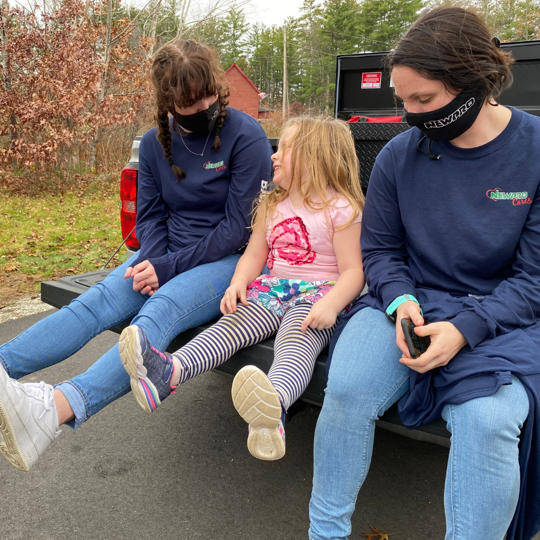 NEWPRO employees sit on the tailgate of pickup truck with homeowner's child